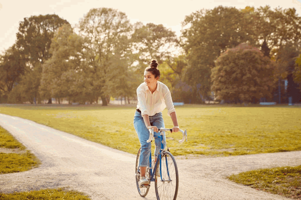 Young woman riding bike at a park