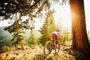 Female mountain biker riding down ridgeline trail
