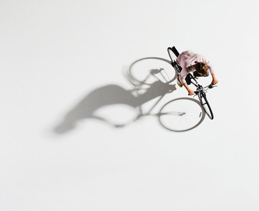 Man riding hybrid bike on white background
