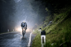 man cycling a hybrid bike on wet road